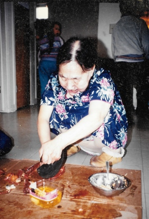 This Puvirnituq elder, who hosted my first country foods meal in November 1991, deftly slices caribou with an ulu. (PHOTO BY JANE GEORGE)