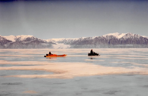 A snowmobile and qamutik leave Pond Inlet, 1994. (PHOTO BY JANE GEORGE)
