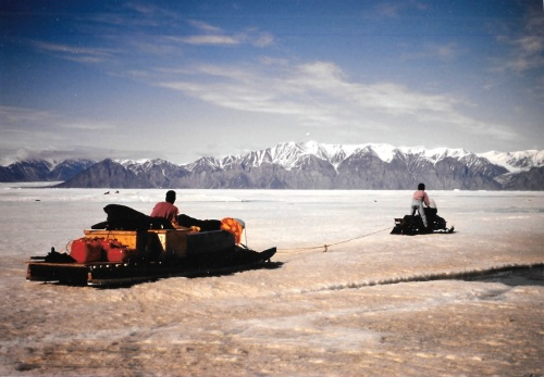 A heavily-laden komatik pulled by a snowmobile heads out of Pond Inlet on the ice in the mid-1990s. (PHOTO BY JANE GEORGE)