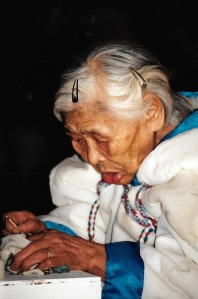 Rosie Iqallijuq, 91, lights the qulliq at the Return of the Sun ceremony in Igloolik in 1997. (PHOTO BY JANE GEORGE)