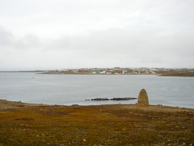 In the forefront, a cairn built by Jan Wanggaard, the half-submerged Maud and the town of Cambridge Bay. (PHOTO BY JANE GEORGE)
