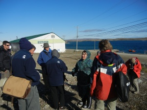Jessie Tologanak tells a group of cruisers the legend of Mt. Pelly, seen in the distance beyond. (PHOTO BY JANE GEORGE)