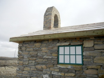 Here you can see the new roof of the old stone church and the plywood now covering the windows. (PHOTO BY JANE GEORGE)
