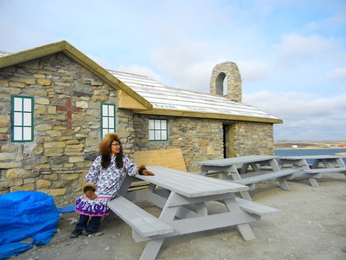 Ida Neglak sits in front of the newly-renovated old stone church.  (PHOTO BY JANE GEORGE)