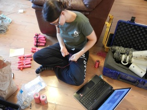 A young researcher prepares sample containers on the living room floor. (PHOTO BY CAMBRIDGE BAY)
